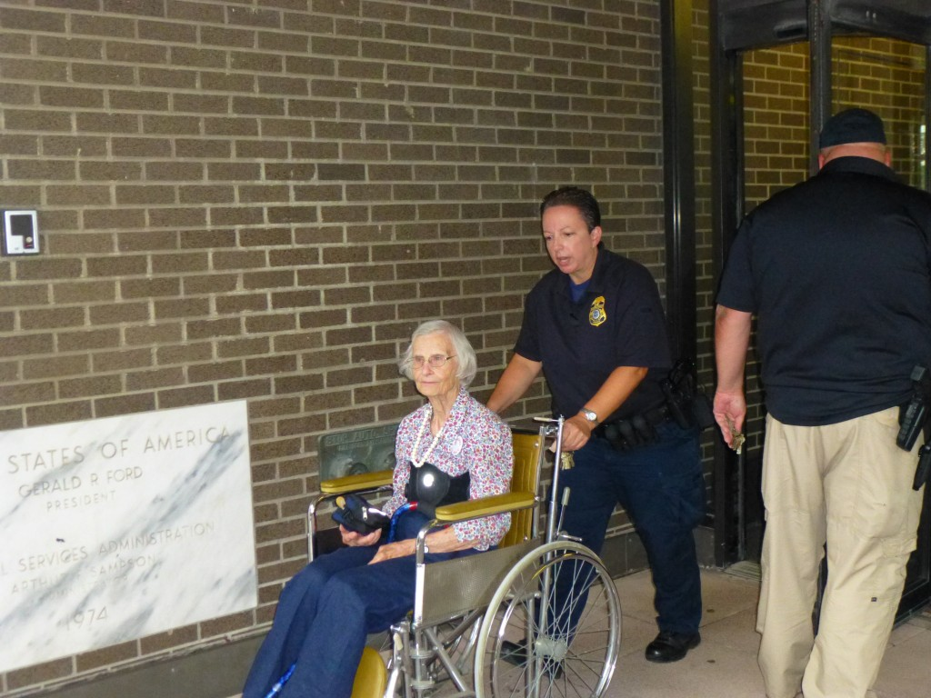 Sue being wheeled out of the building by Homeland Security, photo by Marcia Hopple