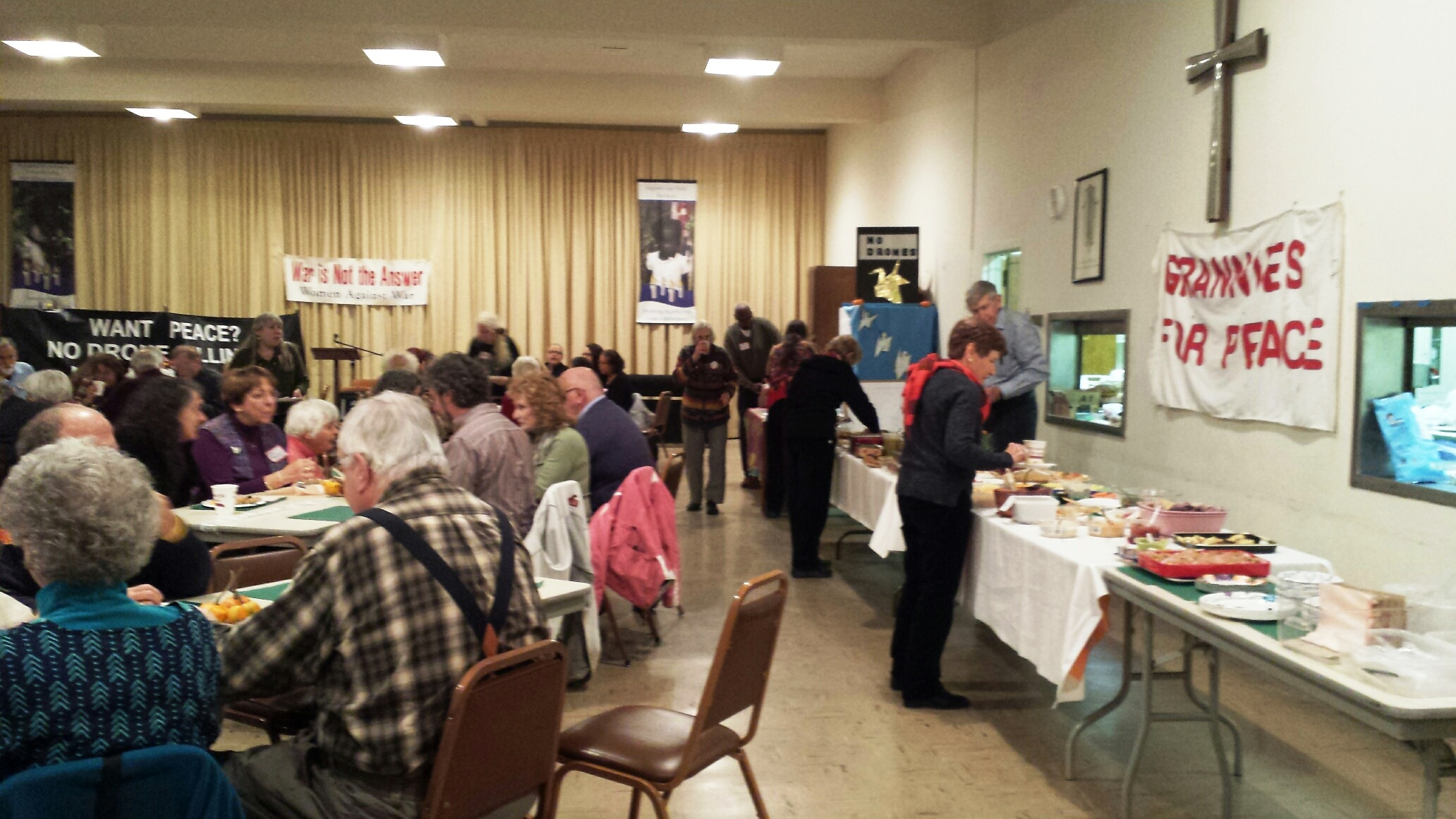 Sumptuous potluck and people enjoying it, photo by Priscilla Fairbank