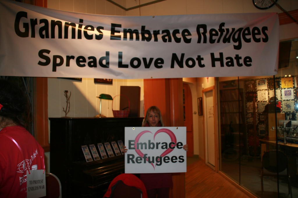 Medea with Embrace Refugees sign.  Photo by Mark Klein