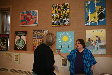 Dahlia Herring telling Maureen about refugees in the Capital District at FUUSA exhibit, photo by Mabel Leon